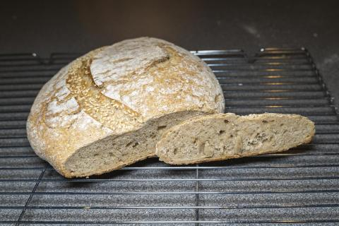 Pic of Overnight Country Blonde boule. It is flat, and it has been sliced open to reveal a dense crumb.