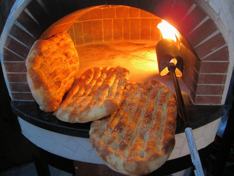 Barbari breads in the process of baking inside the brick oven